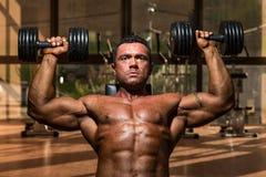 Culturista masculino que hace pesa de gimnasia de la pizca de la prensa del hombro Fotos de archivo libres de regalías