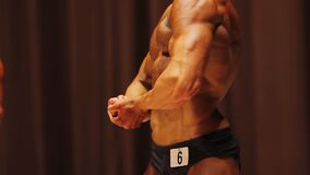 Culturista masculino que presenta para mostrar los brazos y el torso musculares, cuerpo perfecto del ajuste del hombre almacen de metraje de vídeo