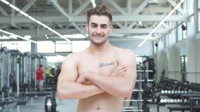 Culturista masculino rubio descamisado atractivo en pantalones cortos dentro en el gimnasio oscuro, mostrando el torso muscular y almacen de video