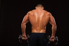 Culturista modelo masculino muscular que hace ejercicios con las pesas de gimnasia, dadas vuelta detrás Aislado en fondo negro co Imagen de archivo