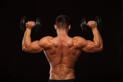 Culturista modelo masculino muscular que hace ejercicios con las pesas de gimnasia, dadas vuelta detrás Aislado en fondo negro co Foto de archivo