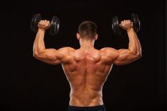 Culturista modelo masculino muscular que hace ejercicios con las pesas de gimnasia, dadas vuelta detrás Aislado en fondo negro co Fotos de archivo