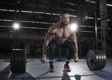 Culturista muscolare attraente che fa i deadlifts in palestra moderna f Fotografia Stock Libera da Diritti