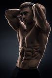 Culturista muscolare bello che posa sopra il fondo nero Immagini Stock Libere da Diritti