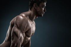 Culturista muscolare bello che posa sopra il fondo nero Fotografia Stock Libera da Diritti