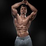 Culturista muscolare bello che posa su Front Lat Spread Fotografia Stock Libera da Diritti