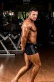 Culturista muscolare che mostra il suo tricipite laterale Fotografie Stock