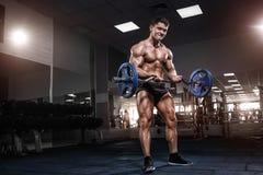 Culturista muscolare dell'atleta nell'addestramento della palestra con la barra Fotografia Stock Libera da Diritti