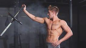 Culturista muscular caucásico que dobla las placas del peso en las barras de hierro en gimnasio, cámara lenta almacen de video