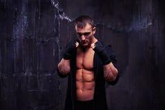 Culturista muscular en un traje negro del deporte que se coloca en el encajonamiento del po Imagen de archivo libre de regalías