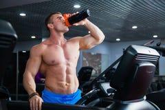 Culturista muscular fuerte que hace ejercicio cardiio en el agua de la bebida de la rueda de ardilla Imagenes de archivo
