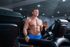 Culturista muscular fuerte que hace ejercicio cardiio en el agua de la bebida de la rueda de ardilla Fotografía de archivo libre de regalías