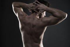 Culturista muscular hermoso que presenta en fondo gris Tiro oscuro del estudio Imagen de archivo libre de regalías