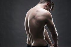 Culturista muscular hermoso que presenta en fondo gris Tiro oscuro del estudio Fotos de archivo libres de regalías