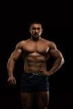Culturista muscular hermoso que presenta en un fondo negro Fotos de archivo