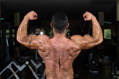 Culturista muscular que muestra su bíceps doble trasero Foto de archivo