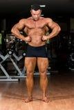 Culturista muscular que muestra su extensión delantera del lat Foto de archivo