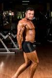 Culturista muscular que muestra su tríceps lateral Foto de archivo