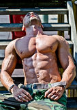 Culturista muscular que pone en las escaleras de madera en el sol Imagen de archivo
