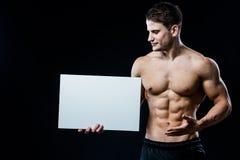 Culturista pieno del corpo con il manifesto bianco in bianco isolato su fondo nero Uomo muscolare bello che tiene bordo grigio fotografie stock