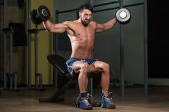 Culturista que ejercita hombros con pesas de gimnasia Foto de archivo libre de regalías
