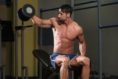 Culturista que ejercita hombros con pesas de gimnasia Foto de archivo