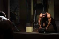 Culturista que hace el ejercicio pesado para la parte posterior Imagen de archivo