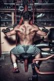 Culturista que hace el ejercicio pesado para la parte posterior Foto de archivo