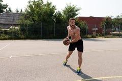Culturista que juega al baloncesto al aire libre Fotografía de archivo libre de regalías