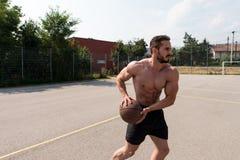 Culturista que juega al baloncesto al aire libre Fotos de archivo