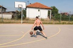Culturista que juega al baloncesto al aire libre Imágenes de archivo libres de regalías