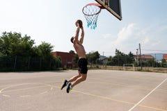 Culturista que juega al baloncesto al aire libre Imagen de archivo libre de regalías