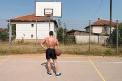 Culturista que juega al baloncesto al aire libre Foto de archivo