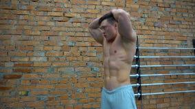 Culturista que presenta en gimnasio en el fondo de la pared de ladrillos almacen de metraje de vídeo