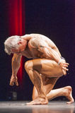 Culturista que se realiza y que se arrodilla abajo en etapa en championshi Imagen de archivo