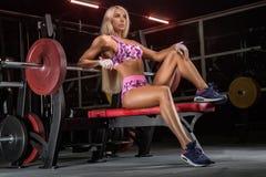 Culturista rubio del atleta de la muchacha hermosa joven que hace un entrenamiento i imagen de archivo