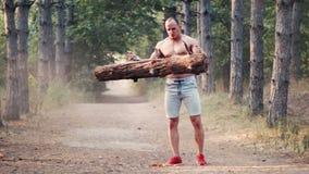 Culturista senza camicia che fa i curlings con il sentiero forestale di collegamento archivi video