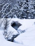 Culvert and stream in winter. A view of a small stream passing through a storm drain or culvert under a roadway during a winter snowfall Royalty Free Stock Images