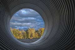 Culvert with sunlit woods royalty free stock photography