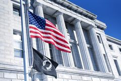 Cumberland County Courthouse Portland Maine. The American and POW flags flying at half staff in front of the Cumberland County Courthouse in Portland Maine on a stock photo