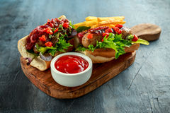 Cumberland korvvarmkorvar med den caramelized löken, grillade röda peppar, fransman steker arkivfoton