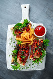 Cumberland sausage hot dogs with caramelized onion, roasted red peppers, french fries. Royalty Free Stock Photo