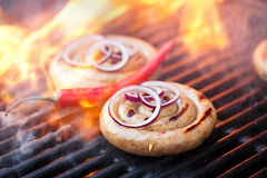 Cumberland sausage, spiral pork sausage on bbq grill with flame, Stock Photography