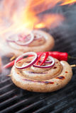 Cumberland sausage, spiral pork sausage on bbq grill with flame, Royalty Free Stock Image