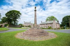 Stone cross in the village of Greystoke, Cumbria. CUMBRIA, ENGLAND - JUNE 14, 2016 - Stone cross in the village of Greystoke, Cumbria. The village is on the royalty free stock photography