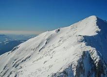 Cume da montanha do pico da neve de Piatra Craiului no witer com céu azul Imagens de Stock