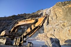 Cumes de Apuan, Carrara, Tosc?nia, It?lia 28 de mar?o de 2019 Uma m?quina escavadora em uma pedreira do m?rmore branco de Carrara foto de stock