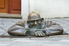Cumil the Peeper sculpture in Bratislava, Slovakia. Cumil the Peeper sculpture, also known as The Watcher or Man at Work, in Bratislava, Slovakia. The sculpture Stock Image