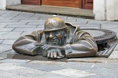 Cumil the Peeper sculpture in Bratislava, Slovakia. Cumil the Peeper sculpture, also known as The Watcher or Man at Work, in Bratislava, Slovakia. The sculpture Royalty Free Stock Photo