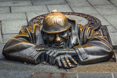 Cumil (The Watcher) or Man at work. Statue of man peeking out from under a manhole cover in Bratislava, Slovakia. Popular attraction was made in 1997 by Stock Photography